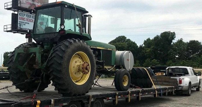 Green tractor on a trailer of a truck ready to be transported, California Tractor Shipping