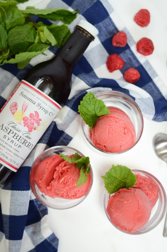 An overhead shot of three servings of Raspberry Meyer Lemon Sorbet and a bottle of Raspberry Syrup lying next to them.