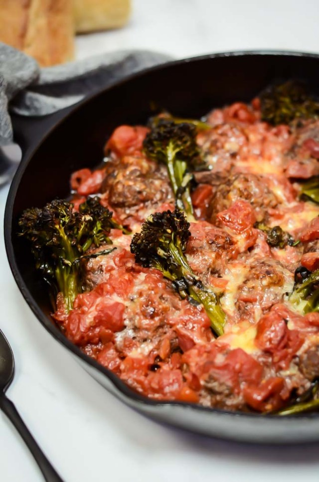 A close-up view of One-Pan Bison Meatballs with Broccolini and Tomato Sauce with some crusty bread in the background.