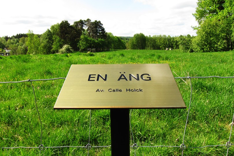 """7 epic sculptures - a sign in front of the art work """"a meadow - by: Calle Holck"""" and behind the sign is a real meadow."""