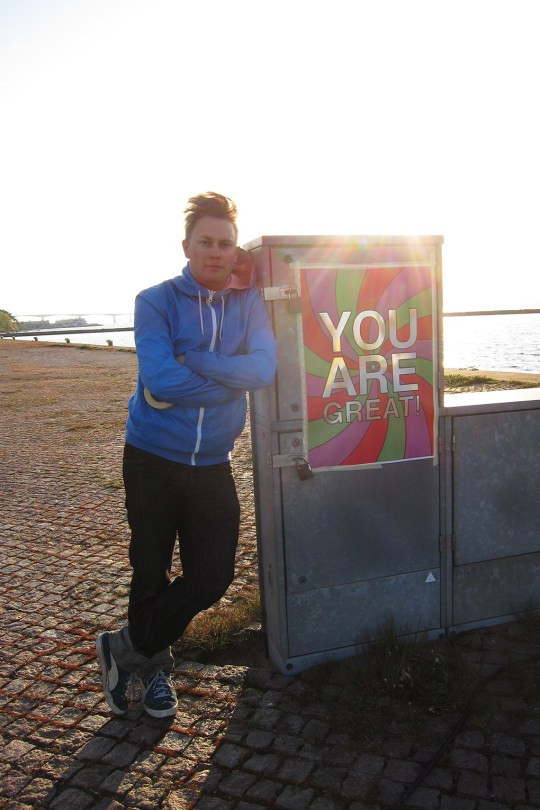 Installation. Artist Calle Holck standing next to a You are great-poster.