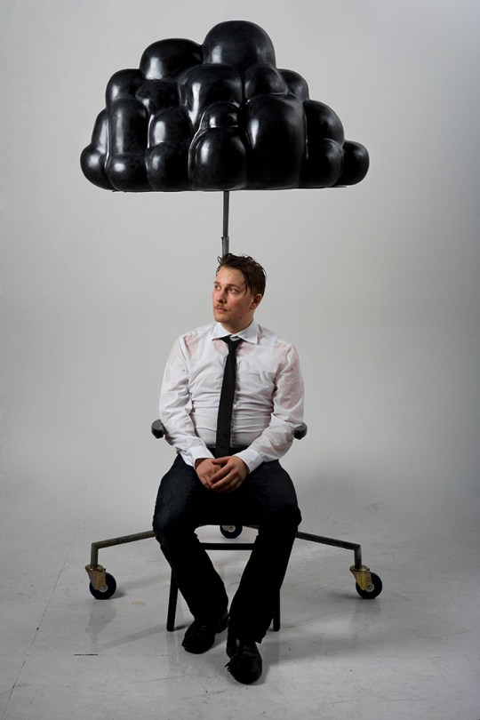Artist Calle Holck sitting under the black cloud. It is raining from the cloud and Calle is soaked.
