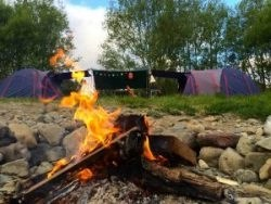 Tent site with campfire on the riverbank at Kaitoke Regional Park