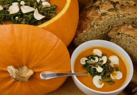 Hollow pumpkin filled with Pumpkin and pepper soup topped with crispy parsnips and kale, served with seeded soda bread