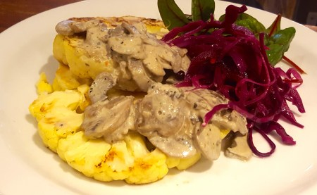 A plate of Cauliflower steaks with mushroom sauce and quick-pickled red cabbage