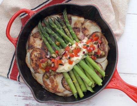 Red cast iron pan with potato galette, asparagus, aquafaba mayo and a salsa