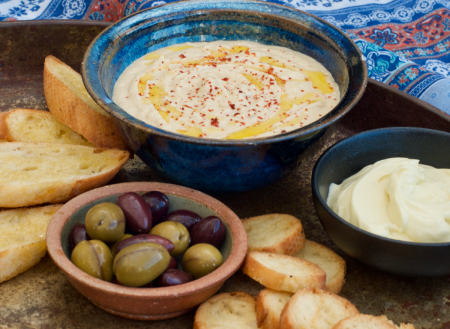 Metal tray with bowl of sesame free Hummus, olives and crostini