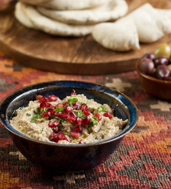 A blue pottery bowl of moutabel garnished with chopped parsley and pomegranate seeds on a kilm rug