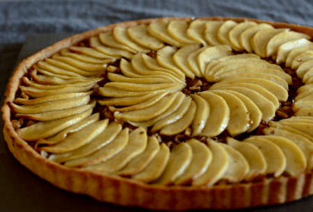 A plant-based apple tart with thin slices of glazed baked apples arranged on 2 circles