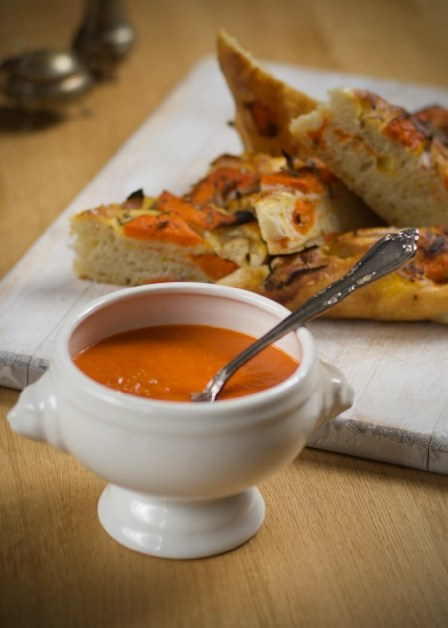 a bowl of red pepper soup with wedges of butterkin focaccia