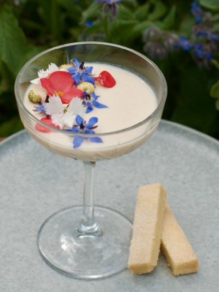 Champagne glass filled with lemon posset decorated with edible flowers and white strawberries served with shortbread