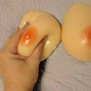 photo of a hand squeezing one of the two breast forms alongside the other from the pair