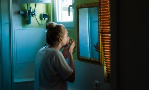Woman picking her skin in front of her bathroom mirror. Excoriation skin picking Trichotillomania BFRB Treatment in Fullerton anaheim brea orange county