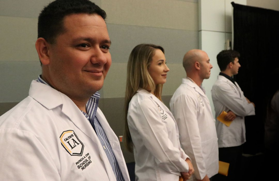 Nursing students stand together during their white coat ceremony