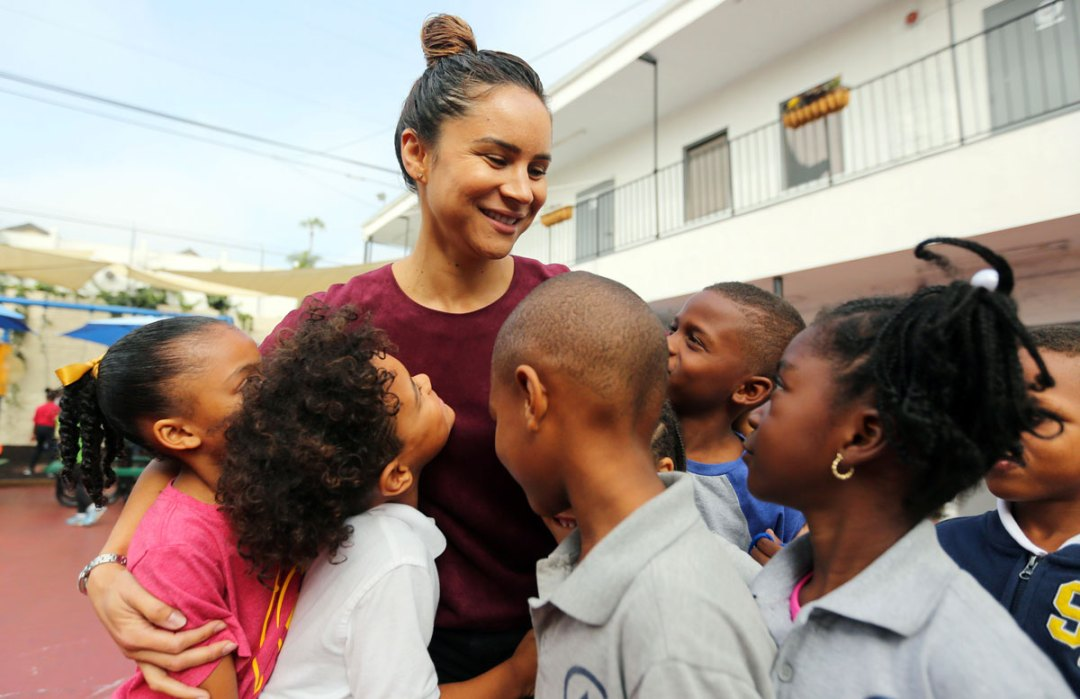 Hattie Mitchell with a group of smiling Crete Academy students.