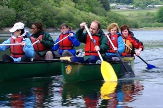 A group are with the instructors in a canoe. They are obviously having fun. Other canoes are visible behind.