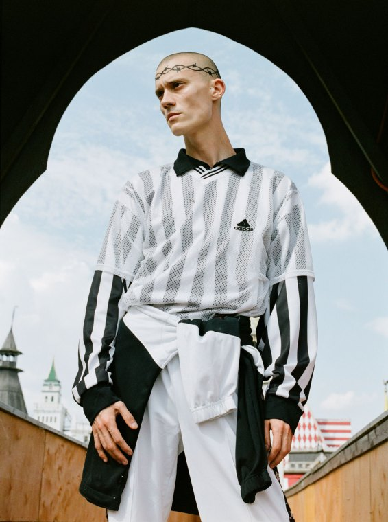 Angel Ulyanov, a Russian queer creative, wearing black and white Addidas top and a barbed wire tattoo circling his head.