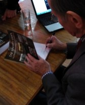 Dr.Denley Owen signs his book