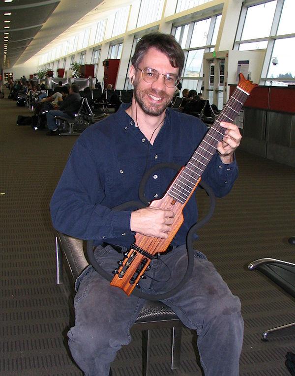 Brent VanFossen in Prague Airport with his practice guitar