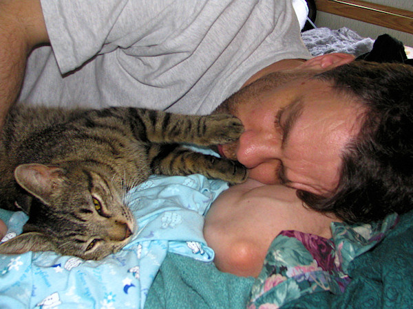 Brent napping with kitten Holiday with paws on his face