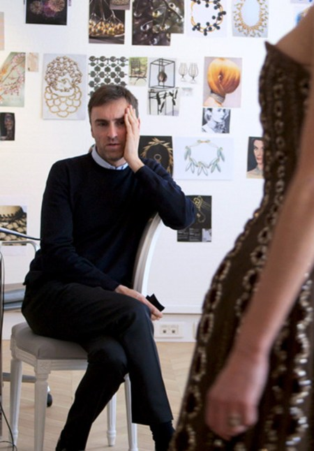 Raf Simons hold his hands to his face while considering a dress design.