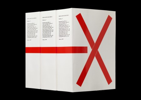 Three volumes of I—X, a generously sized monograph with a white cover and a bright red X on the cover.