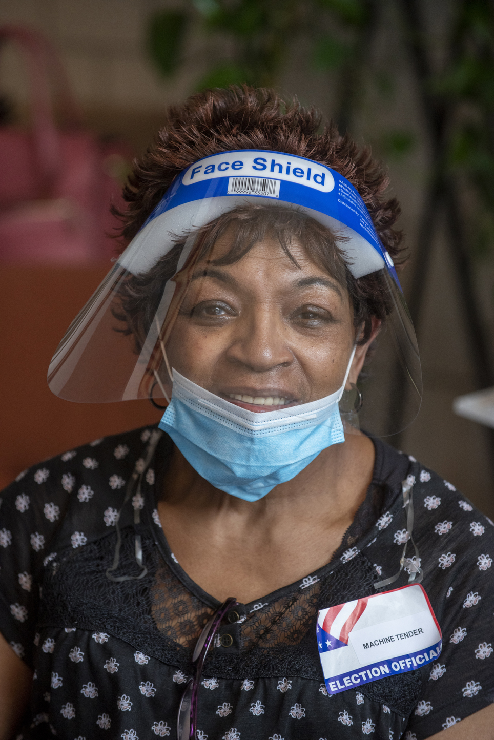 A portrait photo of a poll worker wearing a face shield and mask