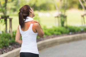 runner holding her shoulder due to pain