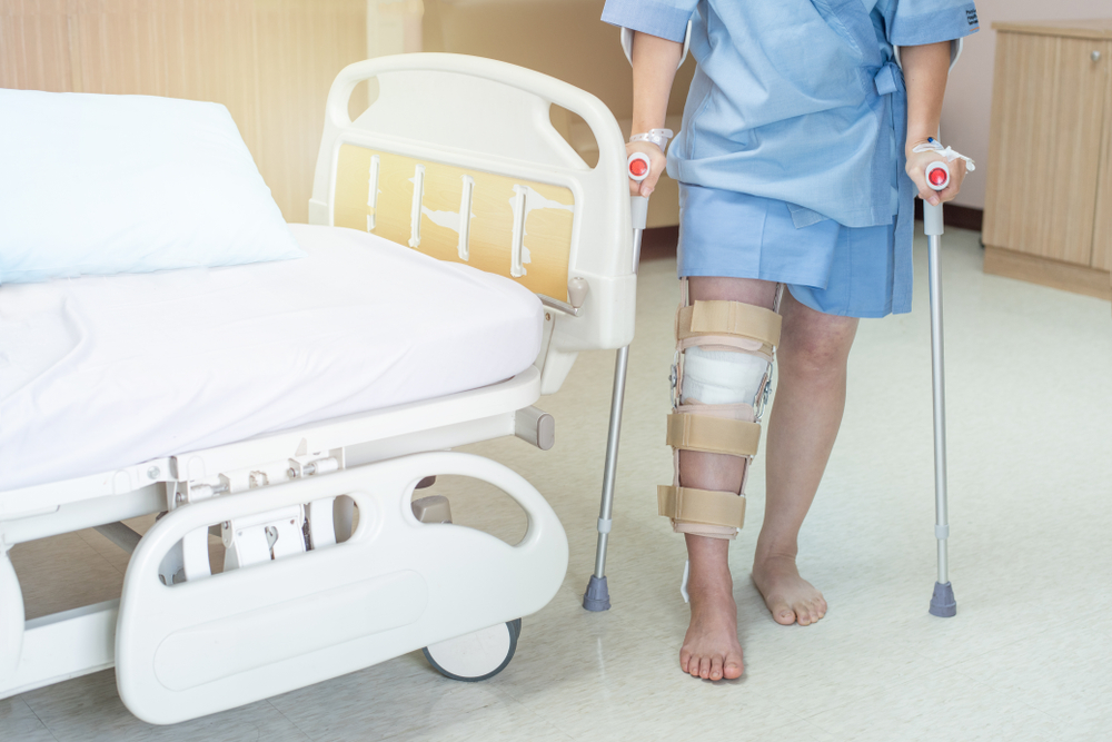 woman patient with knee brace with walking stick in hospital ward