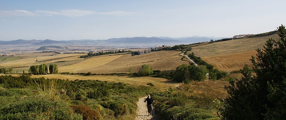 Pèlerin marchant en demi-montagne vers Compostelle