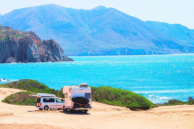 Ein Camper und ein PKW an einem Strand in Sardinien.