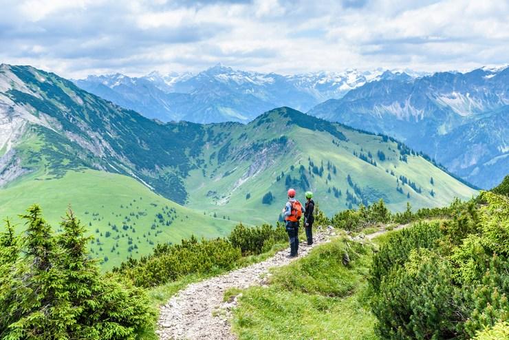 Wanderer in grüner Berglandschaft. Im Hintergrund sind schneebedeckte Gipfelketten zu sehen.