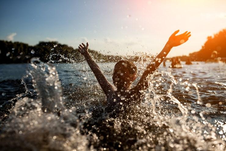 Kind badet im See bei Sonnenuntergang
