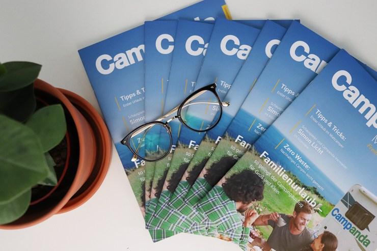 Print Magazine aufgefächert, mit Pflanze und Brille als Dekoration.