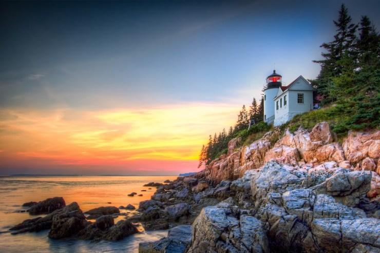 Ein Leuchtturm thront auf der felsigen Küste vor der untergehenden Sonne.