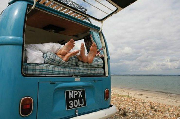 Zwei Paar Füße gucken aus der offenen Heckklappe eines Retro-Campervans.