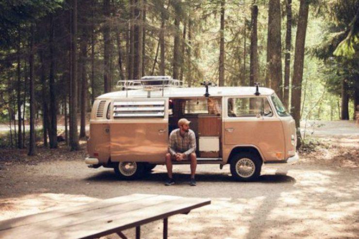 Mann sitzt in einem geparkten Camper in einem Wald.