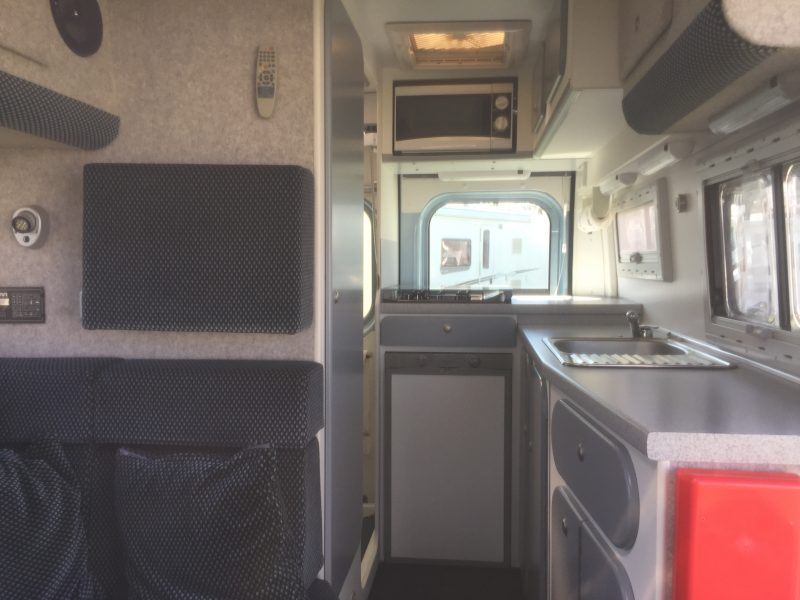 Campervan with side washroom division and corner kitchen