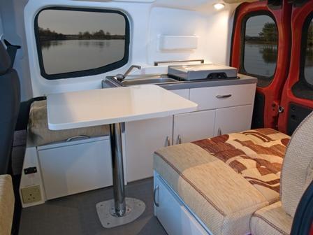 Innvendig i bobilen med bord og sofa med kjøkken i bakgrunnen