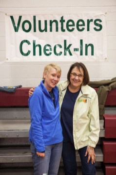 Two smiling women standing under Volunteer Check-In banner