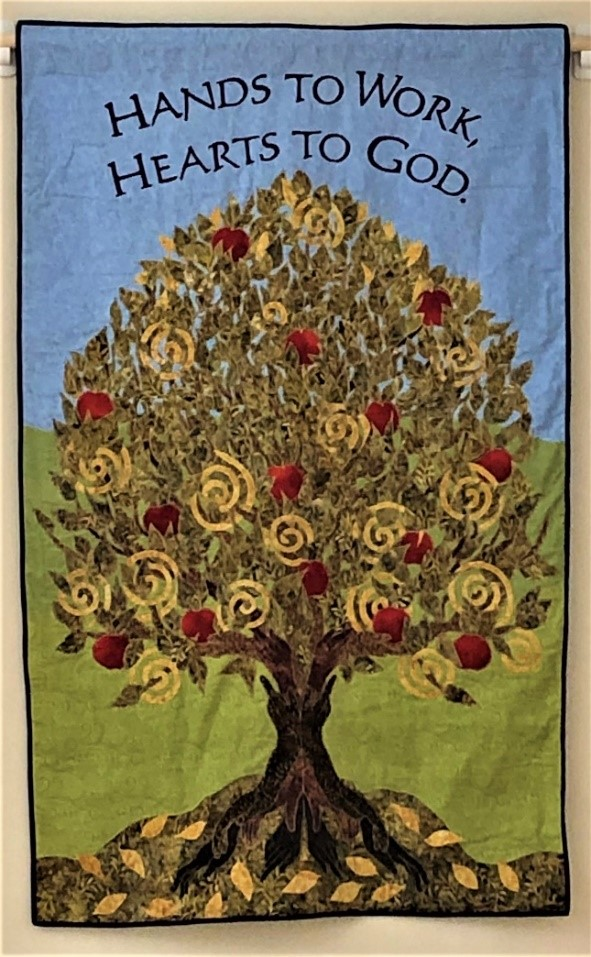 "fabric art banner depicting the tree of life in greens and with red apples with the Celtic spiral in the tree leaveswith the Shaker proverb ""hands to work, hearts to god"""
