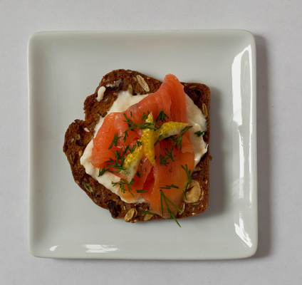 Smoked salmon with horse radish cream. Combine sour cream or crème fraîche with a spoonful of horseradish and some finely chopped fresh dill. Spread mixture on triangles of pumpernickel bread. Top with a slice each of cucumber and smoked salmon.