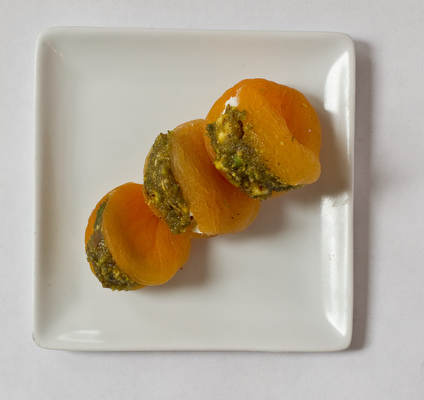 Moroccan stuffed apricots. Slit plump, soft, dried apricots and fill with goat cheese, then top with a mixture of ground pistachio, honey and lemon juice and finely grated zest.