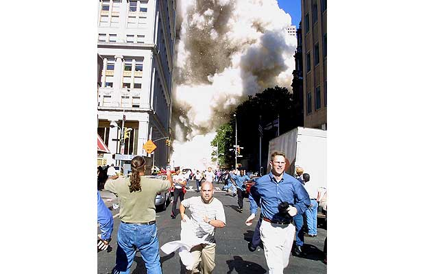 Pedestrians run from the scene as one of the World Trade Center Towers collapses September 11, 2001 in New York.