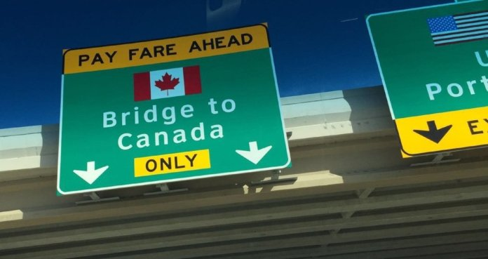 A highway sign that shows the way for those moving from the US to Canada.