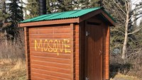 """[A photo of an outhouse, with the word """"MOSQUE"""" spray-painted on the side.]"""