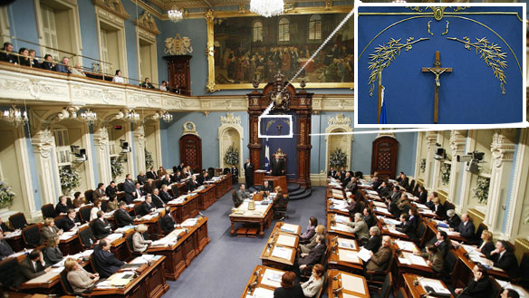 [A photo of the Québec Assemblée nationale in session, with a callout showing the location of the crucifix in its central location above the Speaker's chair.]