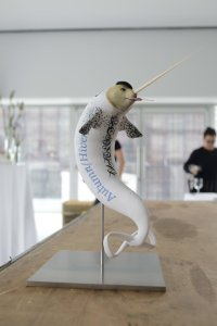 "[A photo of a statuette of a bizarre creature that looks like a white narwhal with a fairly anthropomorphic, flesh-coloured face. It is sucking on a lollipop, wearing a black beret, and it has the words ""Autumn/Hiver"" in decorative text along its side. Its tail fin is shaped like an infinity symbol.]"