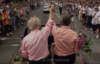 "[A screen capture from the Jim Egan ""Heritage Minute"", showing footage from the 1995 Toronto Pride Parade, with a shot of Jim Egan and John Nesbit from behind, riding high in a convertible in the parade with cheering crowds on either side. Egan and Nesbits arms are raised, and they are holding hands.]"