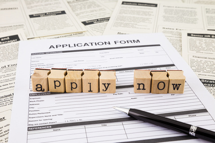 apply now word on wood stamps stacking on application form and fake classifieds ads